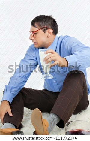 Young male geek making a face while holding glass healthy drink