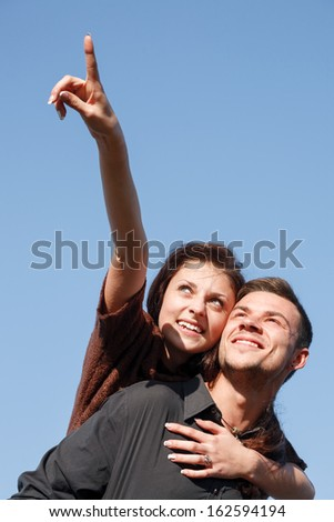 young male giving his girlfriend piggyback ride she pointing up with forefinger blue sky on background - stock photo