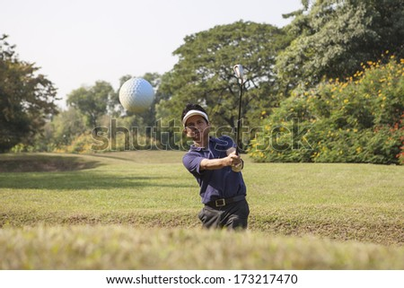 Young male golf player in Blue shirt and grey pants chipping golf ball out of a sand trap with sand wedge and sand caught in motion. - stock photo