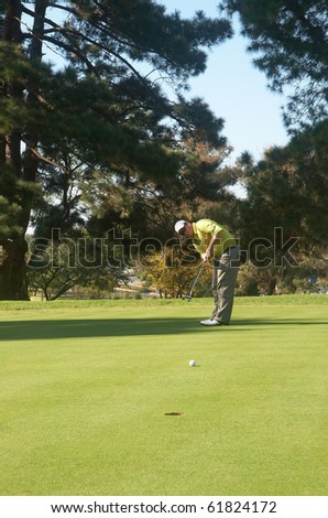Young male golfer hitting the ball on the putting green on a beautiful summer day