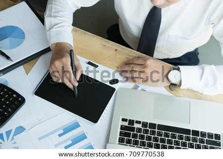 young male graphic designer working with computer. creative man using digital tablet and stylus pen at modern office. business, technology, design and people concept