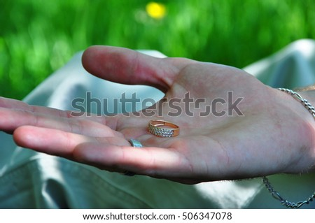 young male hand with open palm holding jewelry engagement ring making proposal or marriage at wedding outdoor