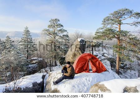 Young male hiker is sitting next to his red tent on a big boulder at the winter mountain base camp on a cold sunny day. Winter camping. Winter hiking clothes. - stock photo