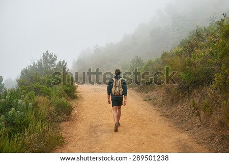Young male hiker walking away from the camera on a dirt path in a nature reserve on a misty morning - stock photo