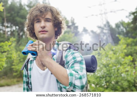Young male hiker with binoculars in forest - stock photo