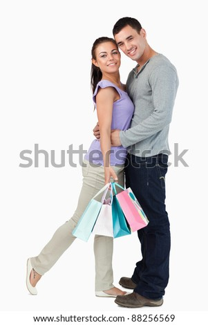 Young male hugging his girlfriend during shopping tour against a white background