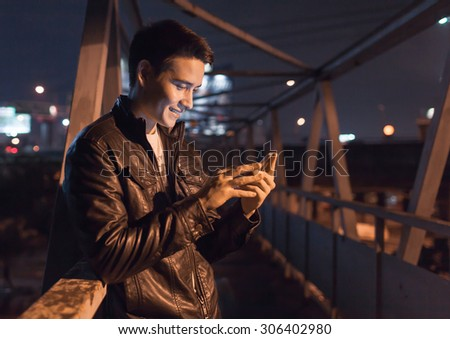 Young male in the city using his smartphone.  - stock photo