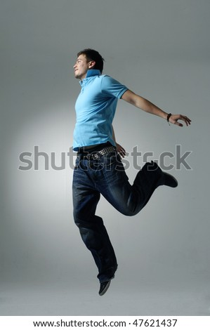 Young male jumping on light background