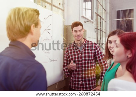 Young Male Leader Listening to his Colleagues During a Meeting About the Project at the White Board. - stock photo