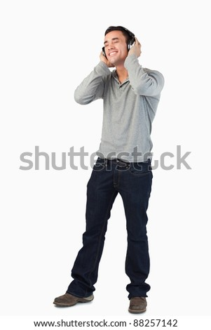 Young male listening to music with headphones on against a white background