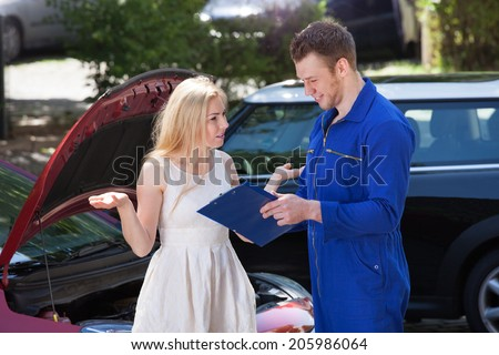 Young male mechanic showing clipboard to angry woman by breakdown car outdoors - stock photo