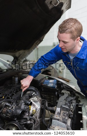 Young male mechanic working on car engine - stock photo