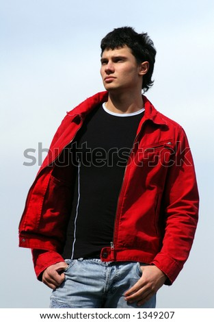 Young male model in a red jacket waiting for somebody