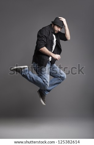 young male model jumping,holding his hat and looking at camera on grey background