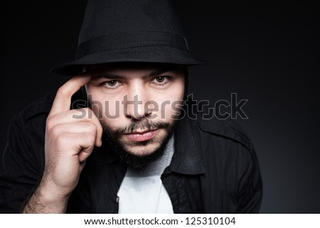 young male model wearing a hat touching his head with his finger on dark background