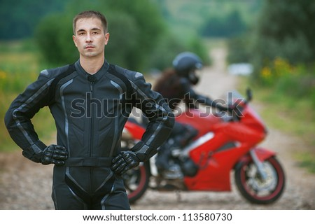 Young male motorcyclist on background of beautiful bike. - stock photo