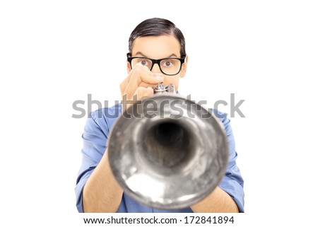 Young male musician blowing into a trumpet isolated on white background - stock photo