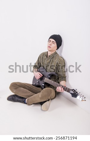 Young male musician is playing a six-string bass guitar is sitting on the floor, in studio. - stock photo
