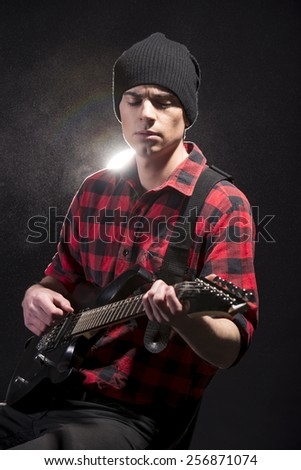 Young male musician is playing a six-string bass guitar on dark background.