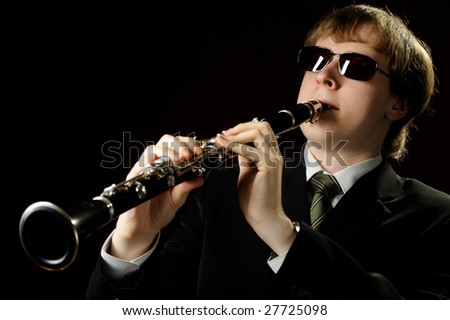 Young male musician plays the clarinet