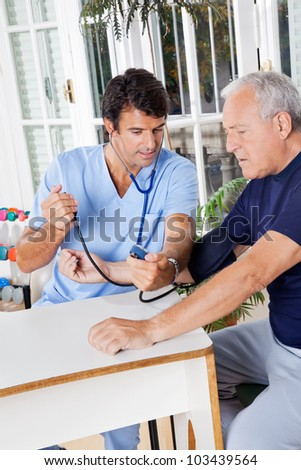 Young male nurse checking blood pressure of a senior patient at hospital