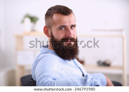 Young male office worker sitting on chair in office , isolated - stock photo