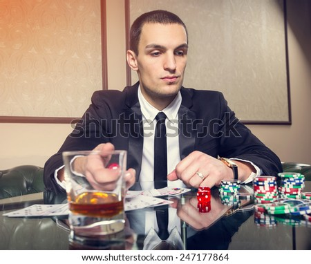 Young male player. Playing cards. Game table, chips, cubes, whiskey, alcohol, gambling, game, casino, gambling house - concept about men's entertainment. Spend time playing cards for money. Gambling. - stock photo
