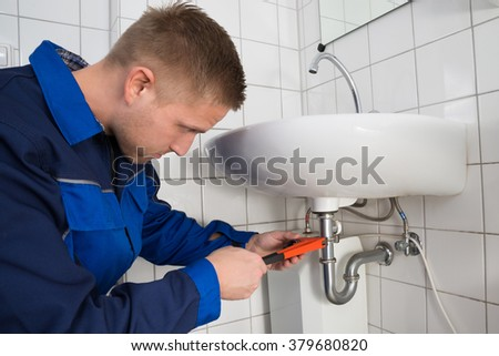 Young Male Plumber Fixing Sink In Bathroom