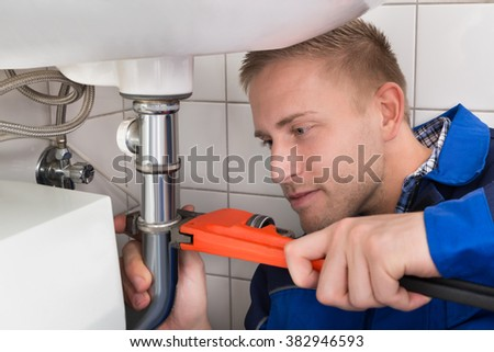 Young Male Plumber Fixing Sink In Kitchen