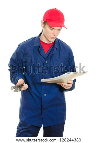 Young male plumber in uniform with wrench reading manual. Isolated on white - stock photo
