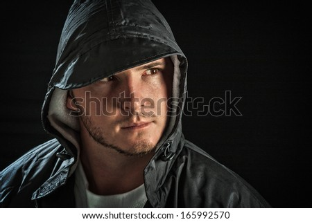 young male posing wearing waterproof hood with dark moody lighting and sombre mood