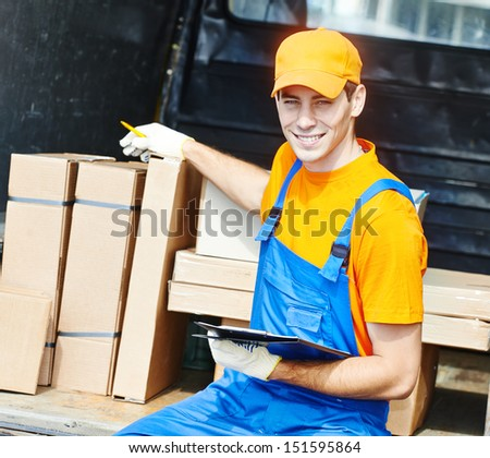 young male postal delivery courier man in front of cargo van delivering package - stock photo