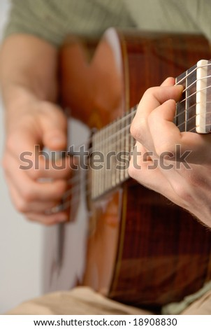 Young male practicing on a classical guitar