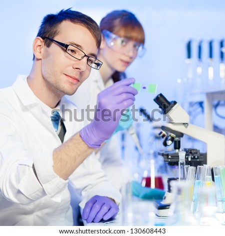 Young male researcher looking at the microscope slide in the life science (forensics, microbiology, biochemistry, genetics, oncology ) laboratory. Female assistant scientist working in the background.