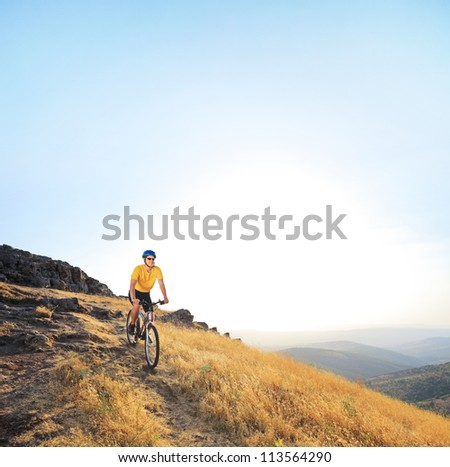 Young male riding a mountain bike on a sunset, Macedonia - stock photo