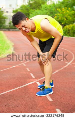 young male runner suffering from knee injury on the track in the stadium - stock photo