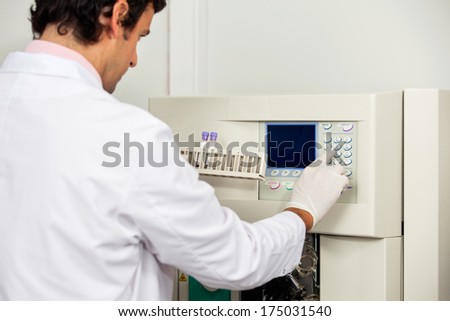 Young male scientist with samples operating analyzer in medical laboratory - stock photo