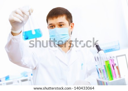Young male scientist working with liquids in laboratory - stock photo
