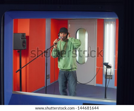 Young male singer recording a track in a studio - stock photo