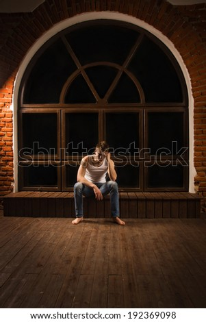 Young male sitting on floor with head down as if sad or depressed  - stock photo