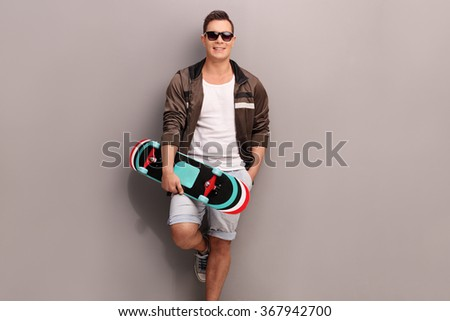 Young male skater holding a skateboard and leaning against a gray wall - stock photo