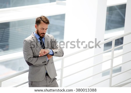 Young male skilled CEO in formal wear checking time while waiting business partners who are be late for a meeting, handsome businessman looking on his luxury watches while standing in office interior - stock photo