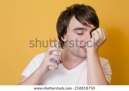 Young male smell parfume  - stock photo
