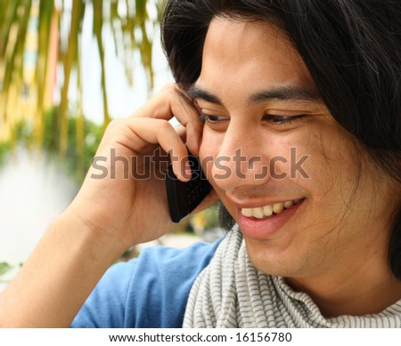 Young Male Smiling and Talking on a Cellphone - stock photo
