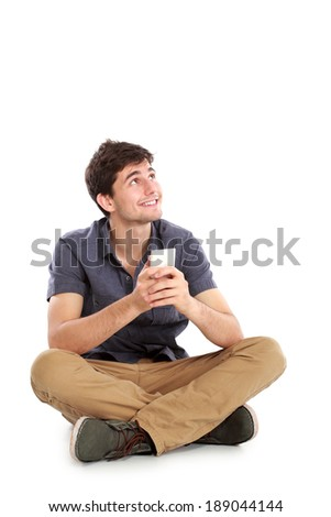 young male smiling using mobile phone thinking and looking up against white background - stock photo