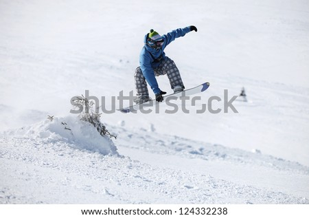 Young male snowboarder jumping on a snowy slope - stock photo