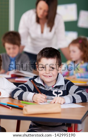 Young male student drawing with pencil at the classroom - stock photo