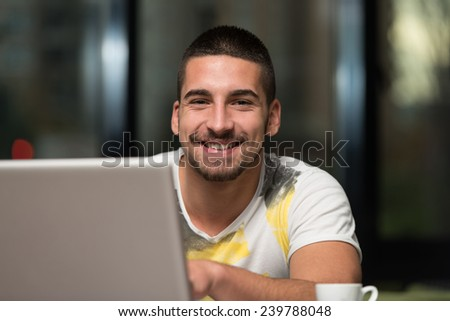 Young Male Student Drinking And Having Fun With Laptop In Cafeteria - stock photo