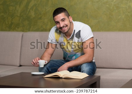 Young Male Student Drinking And Reading Book In Cafeteria - stock photo