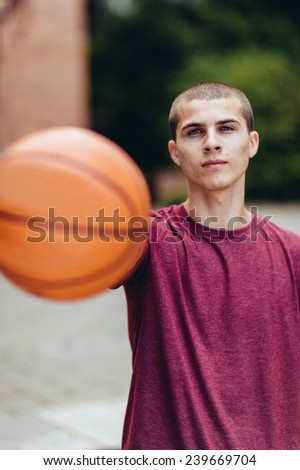 young male student holding basketball, serious face - stock photo